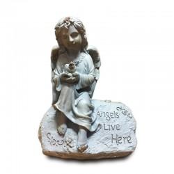 Niña ángel sobre roca